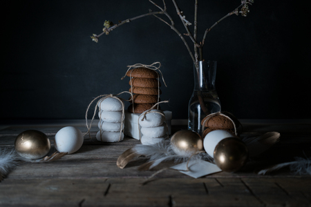 Easter. Easter night. Golden eggs and cakes on a wooden table. White feathers. Vintage. Dark background Stockfoto