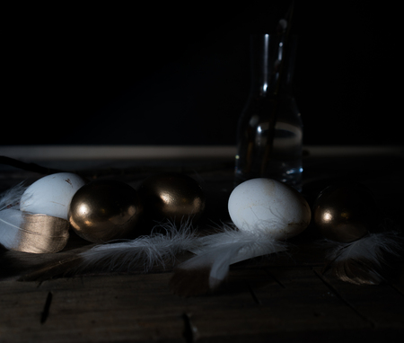 Easter. Easter night. Golden and White eggs, feathers on a wooden table. Vintage. Dark background