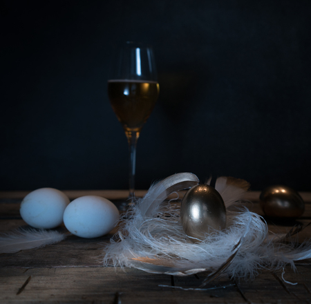 Easter. Easter night. Golden and White eggs, glass of wine, feathers on a wooden table. Vintage. Dark background