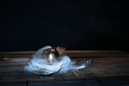 Easter. Easter night. Golden egg, feathers on a wooden table. Vintage. Dark background Stockfoto