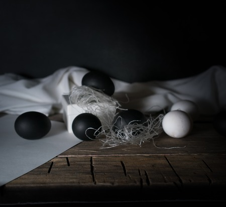 BlackEaster. Easter night. Black and White eggs, feathers on a wooden table. Vintage. Dark background