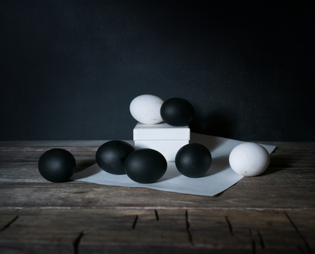 Easter. Easter night. Black and White eggs, feathers on a wooden table. Vintage. Dark background.