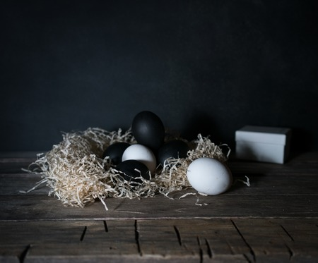 Easter. Easter night. Black and White eggs, feathers on a wooden table. Vintage. Dark background