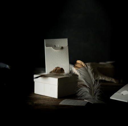 still life. White vintage boxes, gilded feather on a wooden table. Dark background