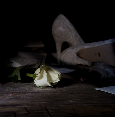 still life. White beautiful shoes and a rosebud on a wooden floor. Dark background Stockfoto