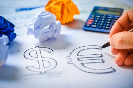 Businessman drawing a dollar sign and a euro sign on white paper Reklamní fotografie