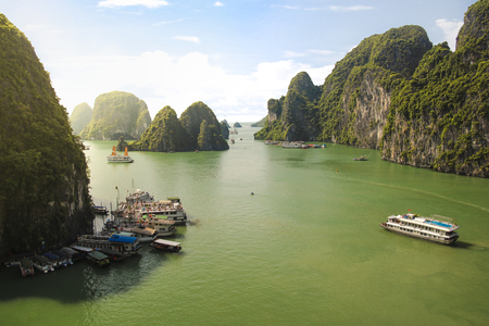 Pier with boats and ships in Halong Bay, Vietnam on a beautiful sunny summer day with ocean, cloudy sky and rocky hills and mountains.