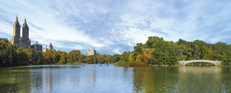 Huge panorama of Central Park in New York City with the Eldorado building and unidentified people rowing in far back during sunny summer day Stock Photo