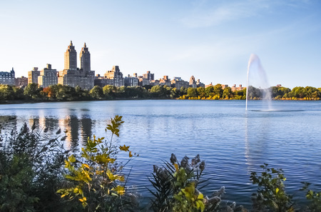 New York City Central Park Jacqueline Kennedy Onassis reservoir with fountain in lake and buildings of Manhattan in background