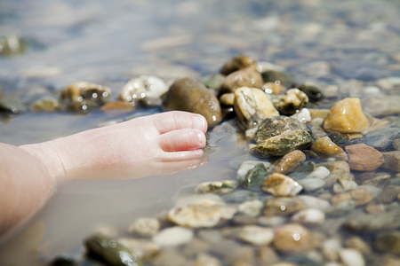 Small child playing with her feet and rocks in lake muddy water during daytime