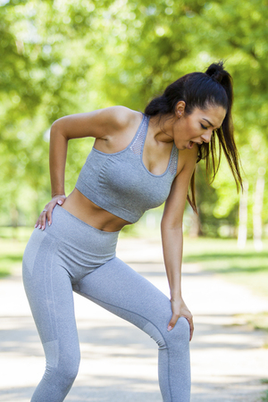 Young fit beautiful girl got back injury of Latissimus dorsi and trapezius muscle during outdoor exercise on a dirt road during summer sunny day