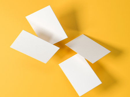 render 3d images of business cards dynamically scattered on a yellow background.