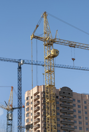 lowering: Three tower crane at a construction site next to the new building