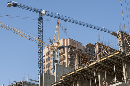 joists: Construction site with tall cranes and metal deck in the foreground