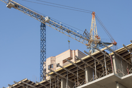 The construction of the walls and floor decks closeup. In the background, cranes and new building