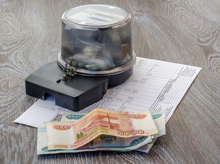 electric meter: medidor de electricidad, dinero, un comprobante de pago de primer plano