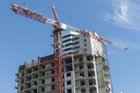cement solution: A new building and red crane on the sky background