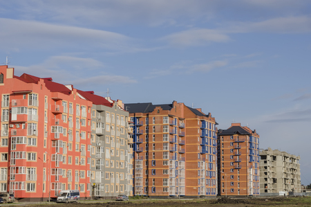 cement solution: New high-rise buildings of pink and brown on a background of blue sky. Stock Photo