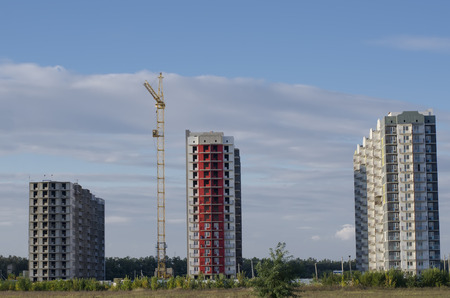 cement solution: Three buildings of different color and yellow construction crane in the open field. Stock Photo