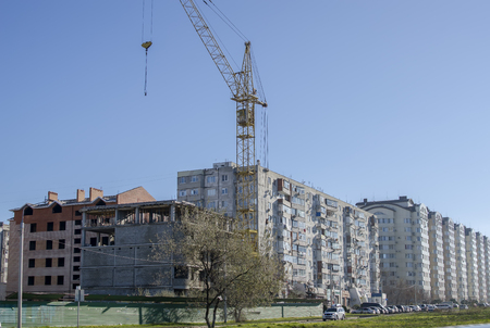 cement solution: Crane over the house under construction on the background of the residential area