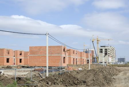 Under construction cottages made of brown bricks against the sky. Stock Photo