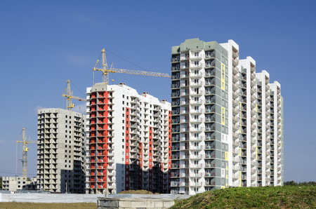 An even row of high-rise buildings with construction cranes against the background of grass and sky.