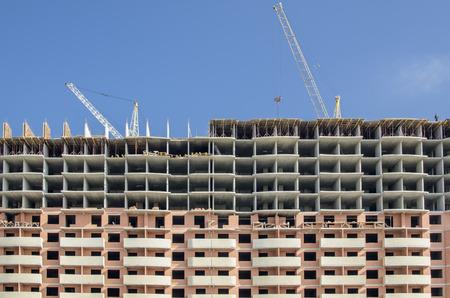 Front view of a monolithic concrete building under construction.