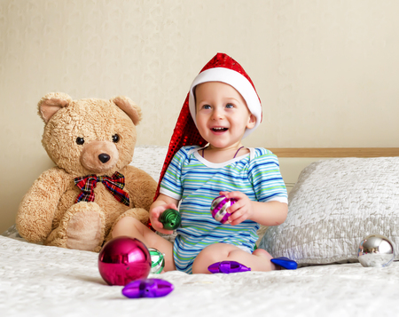 The surprised little boy in a red cap near a toy bear cub. Stock Photo