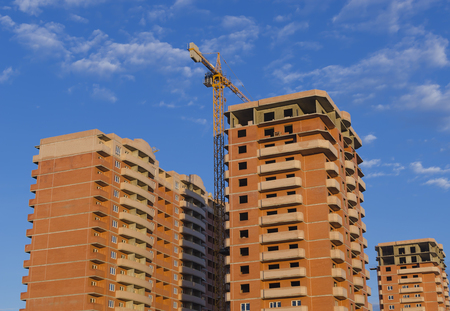 Three new brown brick buildings and a construction crane against a blue sky.