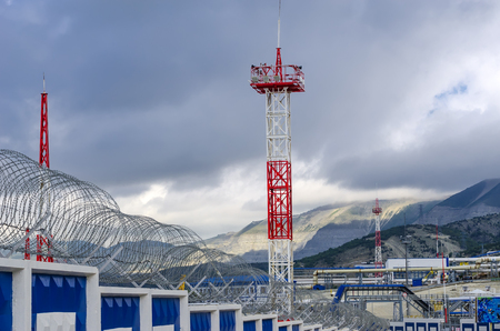 Red mast lightning receiver on the background of the cloudy sky and mountains. 免版税图像