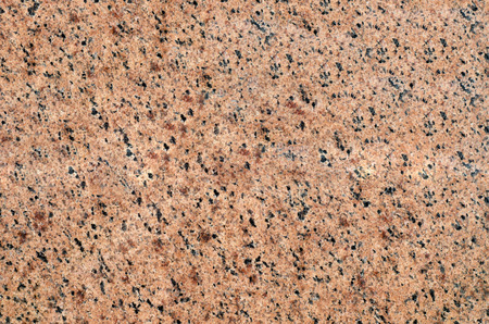 Background of crystal pink granite with black and gray grains.