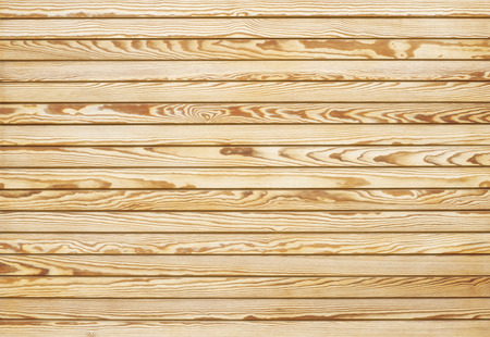 Light wooden background of horizontally located narrow patterned slats. Imagens