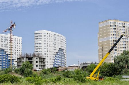 White new buildings, a round house under construction, a high-rise crane, a truck crane against the blue sky and green trees. Stock Photo