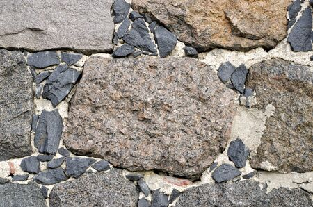 Closeup background of a stone slab from large acute-angle fragments of granite.
