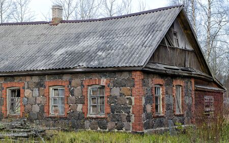 An old non-residential house with walls of granite and brick fragments located in the forest.