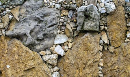 Background of fragments of different sizes of gray limestone and yellow sandstone.