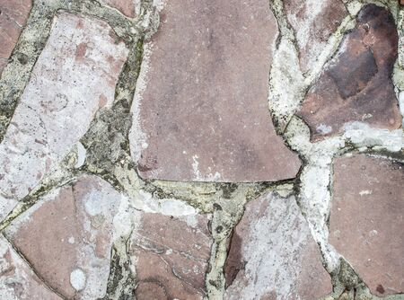 Coarse texture background with pink debris and gray cement close-up.