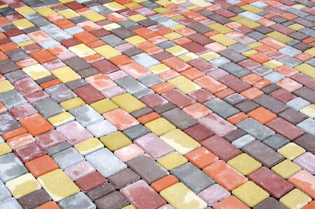 Smooth rows of yellow, pink, brown, gray square and rectangular tiles