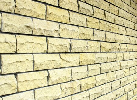 Background wall of yellow rectangular natural stone. Side angle view.