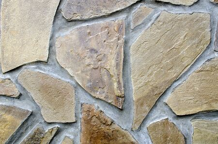 The structure of large fragments of brown sandstone in gray cement close-up. Stock Photo