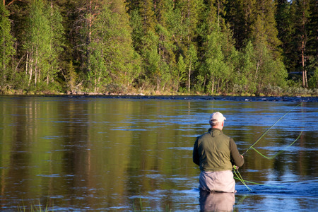 fisher animal: Angler during fly fishing in a river at the evening.