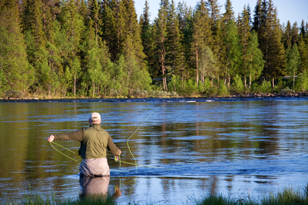 Angler during fly fishing in a river at the evening.