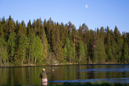 angler: Angler during fly fishing in a river at the evening.