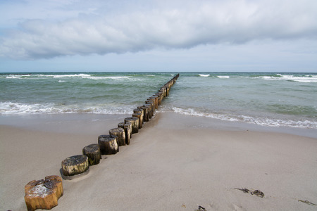 sediment: A groyne is a rigid hydraulic structure built from an ocean shore that interrupts water flow and limits the movement of sediment.