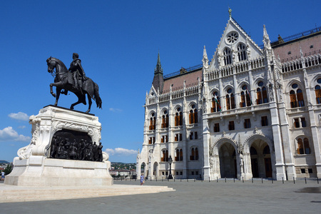 Hungarian parliament building with the equestrian statue of the politician Gyala Andrassy on the bank of the River Danube in Budapest.