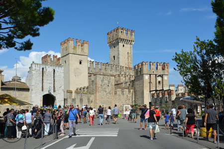 Tourists in front of the Scaligero castle in the historic center of Sirmione on Lake Garda - Italy. Editorial