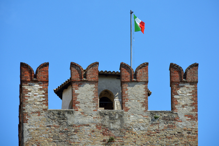 Scaligero Castle in a detail view with the Italian flag in the historic center of Sirmione at Lake Garda - Italy.