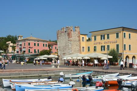 Tourists walking on coastal promenade in Bardolino on the shore of Lake Garda - Italy. Editorial