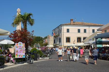 ourists walking on coastal promenade in Bardolino on the shore of Lake Garda - Italy.