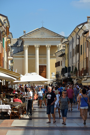 Tourists in Piazza Giacomo Matteotti with the church San Nicolo and Severo in Bardolino on Lake Garda - Italy.
